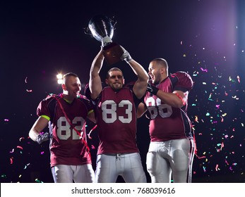 happy american football team celebrating victory with trophy and confetti on the night field