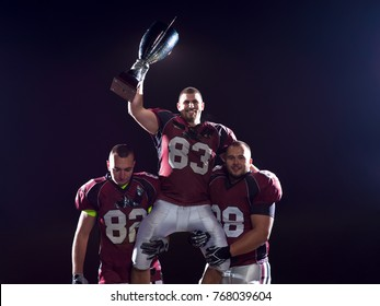 happy american football team with trophy celebrating victory on night field