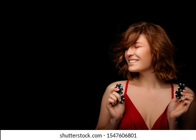 Happy American Girl with a perfect hairstyle and make-up is posing with casino chips in her hands. Casino, Poker and Roulette. Gambling, young rye-haired Woman Lucky casino winnings. isolated.