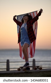 Happy american skater girl with longboard and USA flag