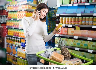 happy american  woman consulting on phone about shopping in supermarket