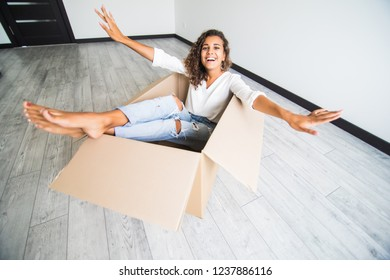 Happy american woman having fun laughing moving into new home. Young woman riding sitting in cardboard box playing while packing unpacking belongings