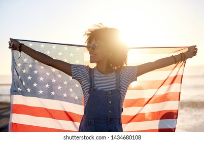 Happy american woman with USA flag, sun flare