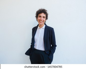 Happy androgynous businesswoman posing in studio. Middle aged woman in office suit standing over white background, keeping hands in trousers pocket and smiling at camera. Business portrait concept
