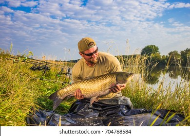 Happy angler with carp fishing trophy.Amur (grass carp).Fish trophy