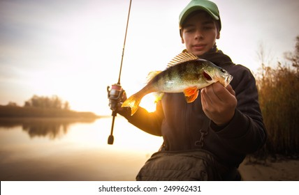 Happy angler with perch fishing trophy