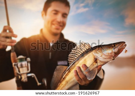Happy angler with zander fishing trophy