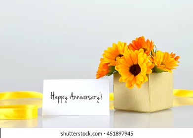 Happy Anniversary card and calendula flowers arranged in gift box