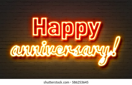 Happy anniversary neon sign on brick wall background