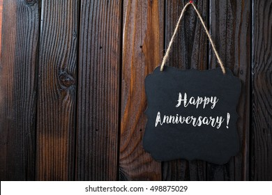 Happy Anniversary Sign Written In Chalk On Chalkboard On Rustic Vintage Wood Background. Top View Selective Focus.