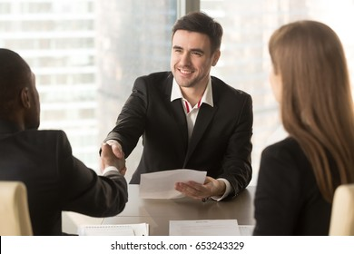 Happy applicant greeting employers at job interview, cheerful satisfied partners shaking hands, making deal agreement with friendly handshake at meeting, successful effective negotiations, get a job