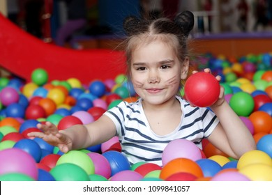 Happy with aqua makeup on her face playing and having fun at kindergarten with colorful balls, family weekend concept, happy birthday and merry party