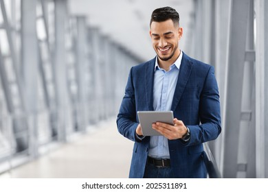 Happy Arab Businessman Booking Hotel Online While Using Digital Tablet In Airport, Handsome Middle Eastern Entrepreneur With Tab Computer Standing In Terminal, Waiting For Flight Boarding, Copy Space