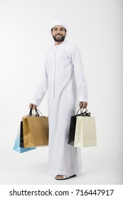 Happy Arab man with a shopping bags standing on white background