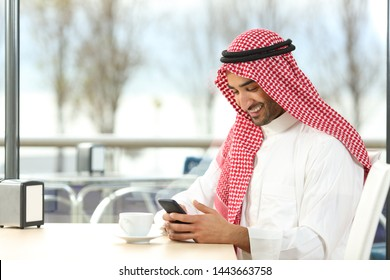 Happy arab man using a smart phone sitting in a coffee shop interior