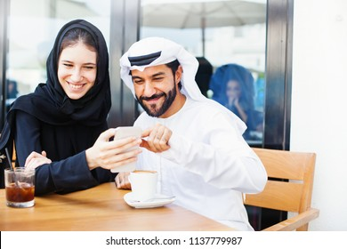 Happy arab middle eastern couple using mobile phone and drinking coffee