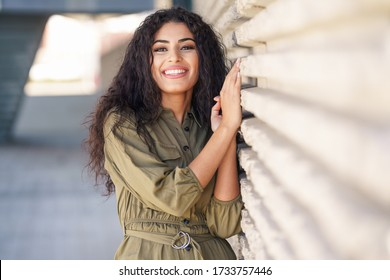 Happy Arab Woman with curly hair in urban background