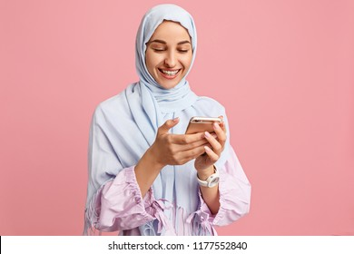 Happy arab woman in hijab with mobile phone. Portrait of smiling girl, posing at pink studio background. Young emotional woman. The human emotions, facial expression concept. Front view.