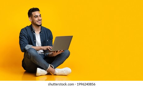 Happy arab young man sitting on floor, using new modern laptop, typing on keyboard and smiling over yellow studio background, looking at copy space for text or advertisement, panorama