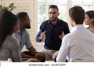 Happy Arabian millennial man speak at group motivational training share idea thought with friends, diverse young people sit in circle talk chat help cope with problems, psychological support concept