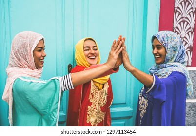 Happy Arabian women stacking hands together outdoor - Young Muslim women having fun and in the university - Concept of empowering, people, religion and team work - Focus on hands