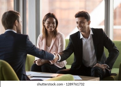 Happy arabic businessman handshaking caucasian man in suit at multi-ethnic meeting, diverse partners shaking hands after signing contract making business deal, international collaboration concept