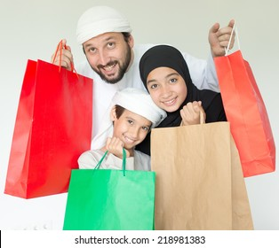 Happy Arabic family with mall shopping bags