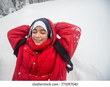 Happy Arabic girl hiking and resting in snow