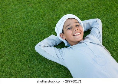 Happy Arabic kid on green grass