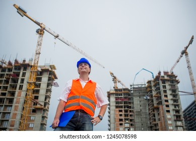 Happy architect on a construction site during a housing project