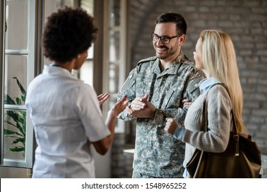 Happy army soldier and his wife communicating with African American healthcare worker while having consultations at the clinic.