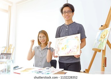 Happy art teacher is showing a portfolio of painting a goldfish of young woman studen in art class.