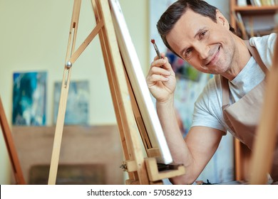 Happy artist smiling in painting studio.