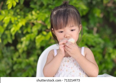 Happy Asia girl eating custard apple/ A cute caucasian girl is hungry and eating fruit on her hands with blurred green tree background