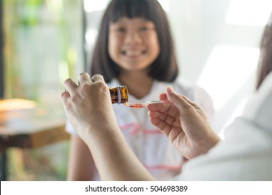 Happy Asia little child girl smiling want to take medicine form mother. Asian kid female waiting to eat drug. Hands of mom pouring cough syrup medicine into clear spoon to daughter.
