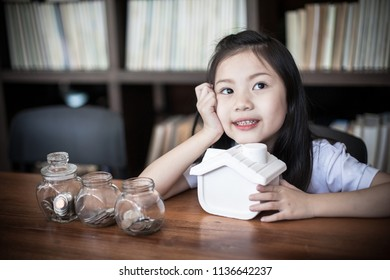 Happy  Asia little girl saving money putting coins into piggy bank . Education, school and money saving concept. Junior Savings Account concept