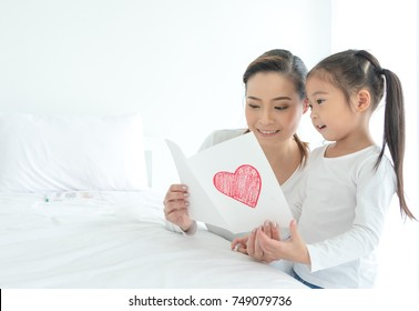Happy Asia mother's day! Child daughter congratulates gives her postcard smiling and hugging. Family holiday and togetherness.