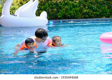 happy asia single dad with son and daughter playing in swimming pool