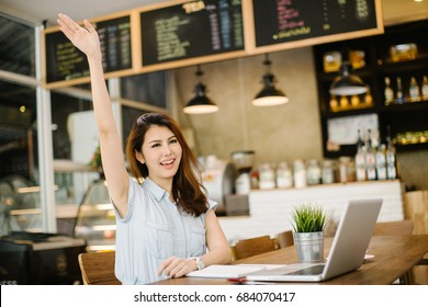 happy Asia woman using laptop while sitting at cafe and greeting her friend.