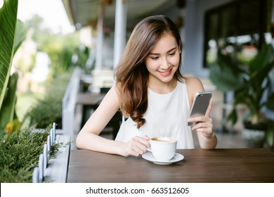 happy Asia woman using smart phone while sitting at cafe.
