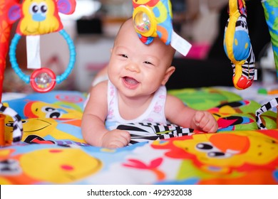A happy asian baby boy at tummy time on the play gym on Bed in Bedroom at Home - Selective Focus
