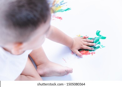 Happy asian baby child use color on hand draw water color or fingerpaint on white paper oneself, Baby 2-3 years