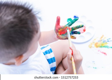 Happy asian baby child use paintbrush draw water color or fingerpaint on hand oneself, Baby 2-3 years