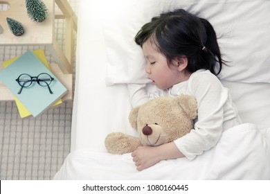 Happy asian baby girl sleeping with teddy bear on the wooden bed in her bedroom, New family and baby protection from mom concept