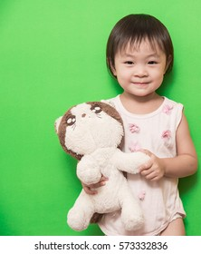 Happy asian baby girl smiling with cat doll on green background