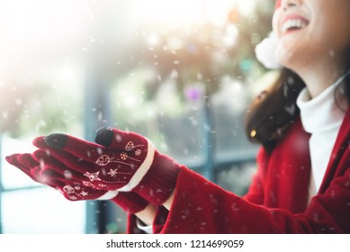 Happy Asian beautiful girl in red sweater clothes raising hands up in the air with snow and snowflakes.