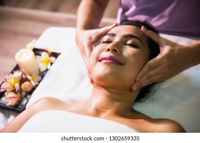 Happy Asian beautiful woman relax in spa club. Body care treatment by Thai oil. Cute girl massage at face by professional massager hands on bed with copy space for text.