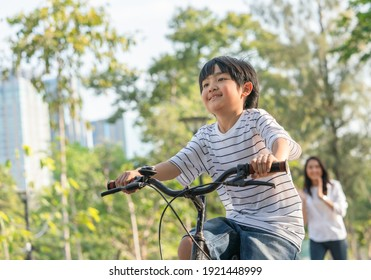 Happy Asian boy can ride a bicycle with the mother looking her son in the background at the park