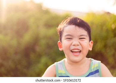Happy asian boy child showing front teeth with smile and laughing : Healthy happy funny smile face kid.Adorable toddler mixed race kid.portrait asian boy at the park.Summer.pediatric kid clinic.