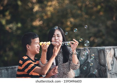 Happy Asian boy with Down's syndrome and mother Blowing bubbles in the park